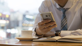 Mão masculina que guarda pronta para fazer a anotação, olhando o telefone celular Ideia do negócio da escrita do local de trabalh Foto de Stock