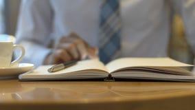 Mão masculina que guarda pronta para fazer a anotação, olhando o telefone celular Ideias do negócio da escrita do local de trabal fotografia de stock royalty free