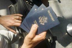 Mão masculina que guarda três U S passports foto de stock