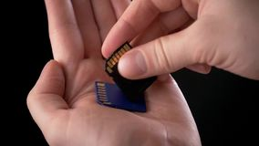 Mão masculina que guarda um cartão do SD do cartão de memória - cartão de Secure Digital usado nas câmaras de vídeo e nos computa video estoque