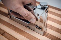 M?o masculina que guarda um grampeador do metal para a madeira na placa fotografia de stock