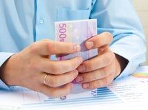 mão masculina que guardara o euro Imagens de Stock