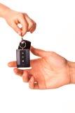 Mão masculina que guardara uma chave do carro e que entrega a sobre Foto de Stock