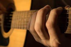 Mão masculina que joga a guitarra acústica na luz natural Foto de Stock Royalty Free