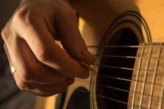 Mão masculina que joga a guitarra acústica na luz natural Foto de Stock