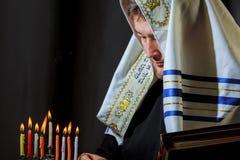 Mão masculina que leve velas no menorah no Hanukkah da tabela imagem de stock royalty free