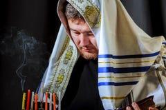 Mão masculina que leve velas no menorah no Hanukkah da tabela fotos de stock royalty free