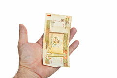 Mão masculina que mantém uma conta dos pesos cubanos isolada no fundo branco Imagens de Stock