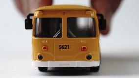 Mão masculina que move um ônibus do brinquedo para a câmera video estoque