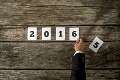 A mão masculina que muda o sinal 2015 em 2016 montou com cartão branco Fotografia de Stock Royalty Free