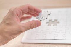 Mão masculina que põe uma parte faltante no enigma de serra de vaivém Imagem de Stock Royalty Free
