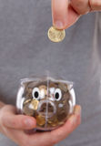 Mão masculina que põr a moeda em um banco piggy Foto de Stock
