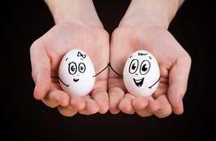Mão masculina que prende ovos engraçados Foto de Stock