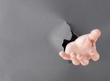 Mão masculina que quebra através do fundo de papel cinzento foto de stock