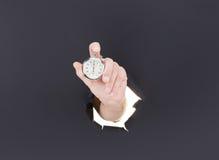 Mão masculina que quebra através do fundo de papel e que guarda o pulso de disparo antigo De alta resolução Fotografia de Stock