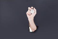 Mão masculina que quebra através do fundo de papel e que guarda o pulso de disparo antigo De alta resolução Fotos de Stock Royalty Free
