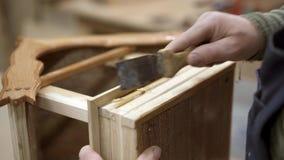 Mão masculina que raspa a colagem endurecida da parte inferior de madeira da caixa de aninhamento filme