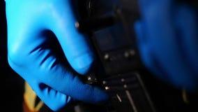 Mão masculina que une o cartucho à espingarda automática e à segurança posta sobre closeup video estoque