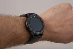 Mão masculina que veste o relógio esperto com a tela vazia no cinza fotografia de stock