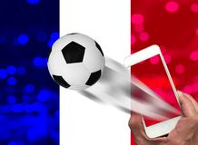 Mão masculina usando o smartphone que olha o campeonato mundial do futebol com fundo da bandeira do bokeh e do franch Foto de Stock Royalty Free