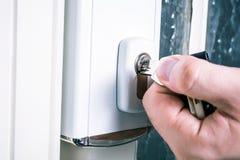 A mão masculina usando uma chave com uma fechadura da porta da segurança, impede o conceito do roubo imagens de stock