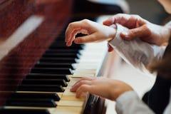 A mão mestra experiente do piano ajuda o estudante fotos de stock royalty free