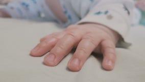 Mão minúscula de um bebê pequeno que encontra-se em uma cama e que remexe-se video estoque