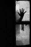 Mão misteriosa em uma janela Foto de Stock