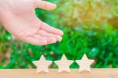 A mão mostra aos três o stasr O conceito do reconhecimento do serviço de alta qualidade e bom Hotel ou café da revisão Avaliação  imagens de stock royalty free