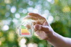A mão mostra a uma energia modelo a casa eficiente fotografia de stock royalty free