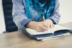 Mão muçulmana da mulher que trabalha e que escreve em um bloco de notas fotografia de stock