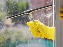 A mão na luva amarela limpa a janela pelo rodo de borracha Fotografia de Stock