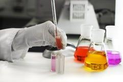 Mão na luva com garrafas do laboratório Fotografia de Stock