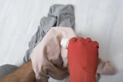 A mão na luva derrama o líquido para lavar na roupa Close-up imagem de stock royalty free