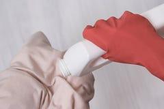 A mão na luva derrama o líquido para lavar na roupa Close-up foto de stock royalty free
