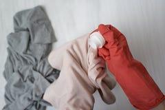 A mão na luva derrama o líquido para lavar na roupa Close-up imagens de stock royalty free