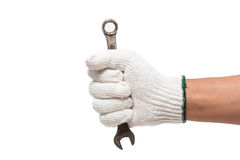 Mão na luva que guarda uma chave inglesa Foto de Stock