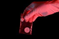 Mão na luva que prende a evidência Imagem de Stock
