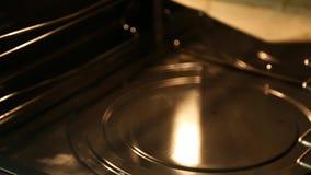 A mão na luva retira do forno, três flatbreads em duas bandejas filme