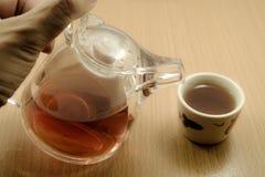 Mão no bule chinês pequeno e no copo de chá chinês Imagem de Stock Royalty Free