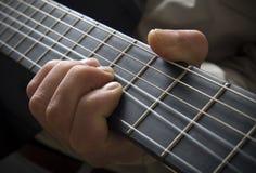Mão no fingerboard da guitarra imagem de stock