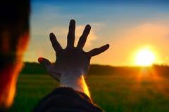 Mão no fundo do por do sol foto de stock