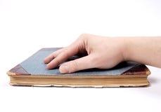 Mão no livro Imagens de Stock