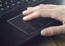 Mão no touchpad do ` s do portátil fotos de stock royalty free