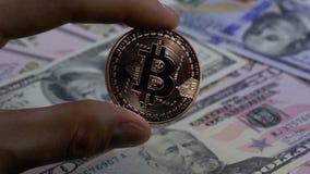 A mão nos dedos guarda uma moeda de bronze Bitcoin, BTC em um fundo com contas dos dólares filme