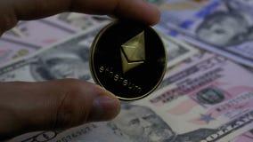 A mão nos dedos guarda uma moeda de ouro Ethereum, ETH em um fundo com contas dos dólares filme