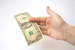 Mão nos estiramentos brancos de um fundo das cédulas no denominatio Imagens de Stock