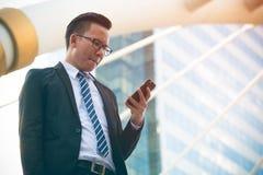 Mão nova moderna do terno do preto do desgaste do homem de negócios que guarda o smartphone Escritório exterior ereto profissiona fotos de stock royalty free