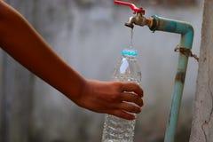 Mão nova que recolhe a água com uma garrafa plástica de uma torneira de água lenta velha do fluxo com grande paciência - esc imagens de stock royalty free