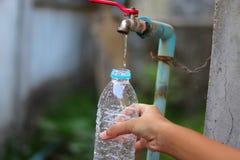 Mão nova que recolhe a água com uma garrafa plástica de uma torneira de água lenta velha do fluxo com grande paciência - esc fotos de stock